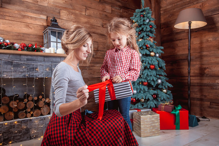 Beautiful happy mother with her daughter open a gift in New Year interior with Christmas tree