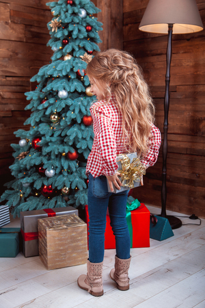 Adorable little girl holding a gift, hiding it behind his back in the New Year room with a Christmas tree.
