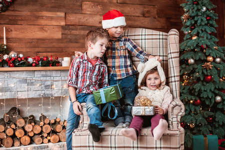 Beautiful children playing with gifts in hand on the armchair in a Christmas interior with Christmas tree and fireplace. The concept of a family holiday Reklamní fotografie