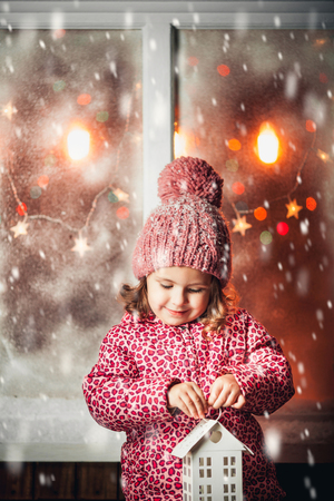 On Christmas night an adorable little  girl laugh with Christmas lantern in hand near the window the snow falls.