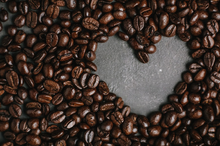 roasted coffee beans, can be used as a background. The concept of Valentines day. Heart of coffee beans Фото со стока