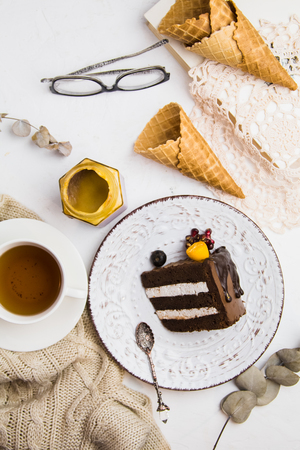A piece of chocolate cake on a white plate with a Cup of tea, glasses and waffles. Sweet lunch. Good morning Imagens