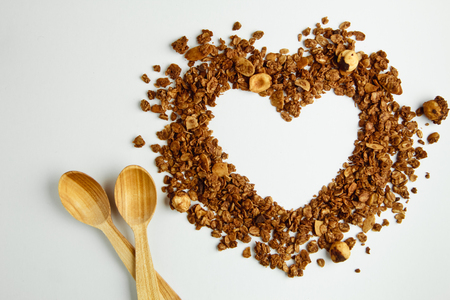Granola on a white background in the shape of a heart with a wooden spoon. The concept of a healthy lifestyle, diet. Happy Valentines day