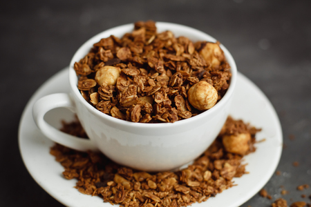 Granola in a white Cup on a black background. The concept of a healthy diet, weight loss, diet Фото со стока