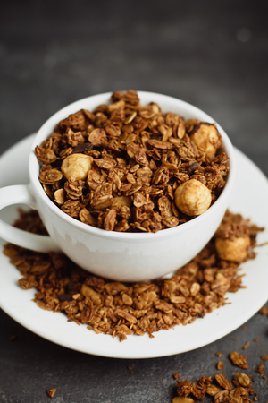 Granola in a white Cup on a black background. The concept of a healthy diet, weight loss, diet 版權商用圖片