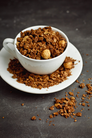 Granola in a white Cup on a black background. The concept of a healthy diet, weight loss, diet Reklamní fotografie