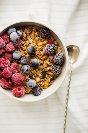 Granola on white wooden background with raspberry and blueberry berries. The concept of a healthy lifestyle, diet, healthy Breakfast