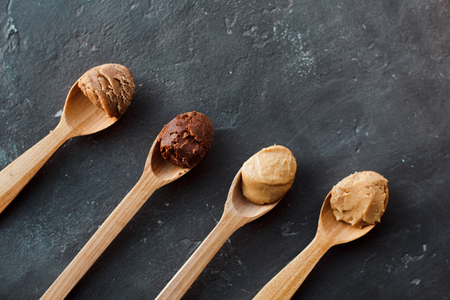 Wooden spoon with peanut butter on a dark background Фото со стока