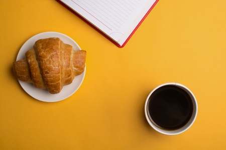 Cup of coffee and enjoy notebook on yellow Background.