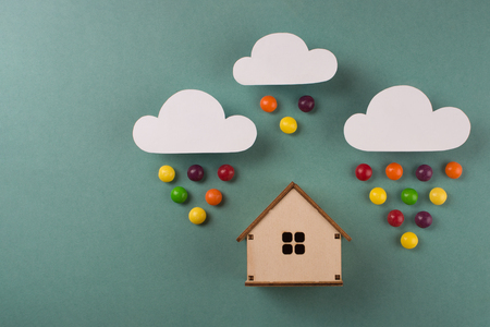 Concept of wooden house on paper with white paper cloud and candy rain. Horizontal composition. Top view.