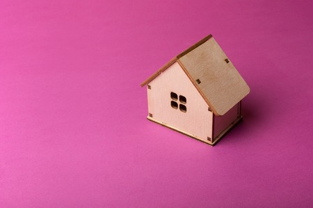 Simply minimal design with miniature wood toy house onmagenta colourful trendy modern fashion background. Stock fotó
