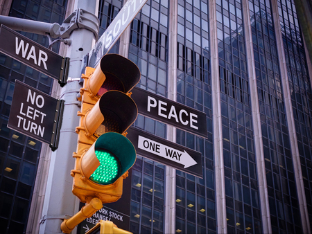 NYC Wall street yellow traffic light black pointer guide one way green light to peace, no turn no way to war. Peaceful, antiwar campaign propaganda. No alternative, lack of option means. Politics 免版税图像