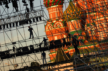 Diagonal view on the workers on stage of construction levels at the Red Square in front of the Vasiliy Blazhenniy Cathedral. Workers shadow figures on staging construction. Pop music stage under construction