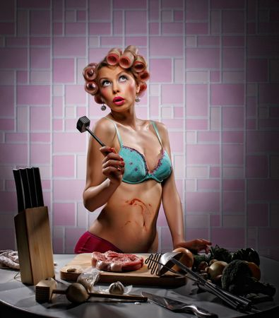 Housewife behind a kitchen table undresses meat photo