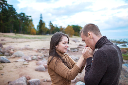 warms: man warms his hands girl on a rocky beach
