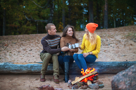 communicates: small company communicates sitting on a log by the fire on the beach against the background of the forest Stock Photo