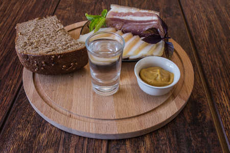 Slicing different types of lard, black bread, mustard and a glass of vodka