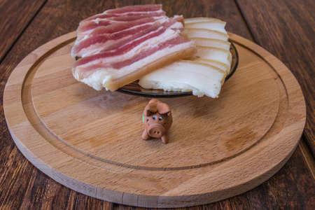 sliced pork fat and a pig figurine