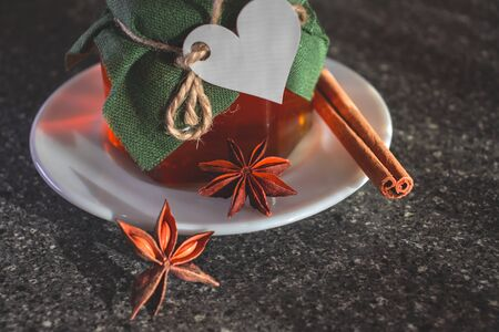 Glass jar with honey covered with green cloth with thread with white paper heart for Valentines Day. White plate. Star anise star anise, cinnamon sticks.