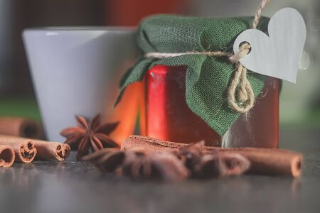 Glass jar with honey covered with green cloth with thread with white paper heart for Valentines Day. Star anise star anise, cinnamon sticks. White cup.