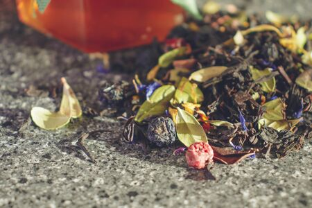 Natural tea brewing of dried berries and leaves of medicinal plants. Glass jar of honey with a lid of natural fabric tied with a thread with a paper heart. Natural products for Valentine's Day.