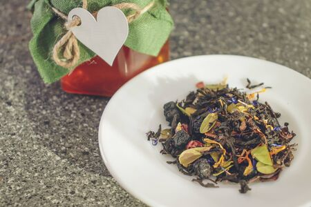 Natural tea brewing of dried berries and leaves of medicinal plants. Glass jar of honey with a lid of natural fabric tied with a thread with a paper heart. Natural products for Valentines Day.