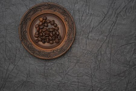 Homemade saucer made of glazed clay. A pinch of brown roasted aromatic coffee beans. Stock fotó