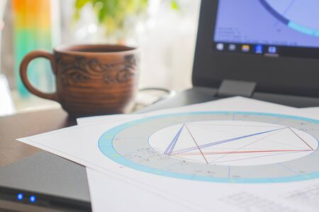 Workplace of a modern astrologer. Astrological charts, diagrams, tables scattered around the table. A cup of aromatic coffee on the table. Black laptop.