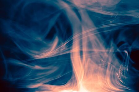 Clouds of colored flowing smoke on a dark background. Smoky extravaganza. Flying smoky vague fantasies.