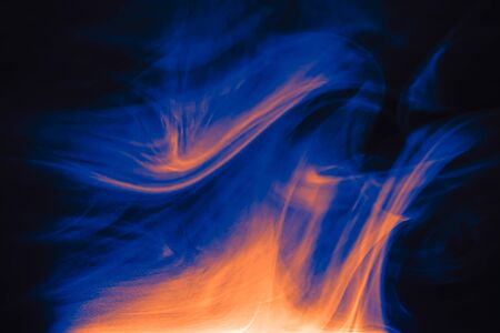 Clouds of colored flowing smoke on a dark background. Smoky extravaganza. Flying smoky vague fantasies. Stock fotó