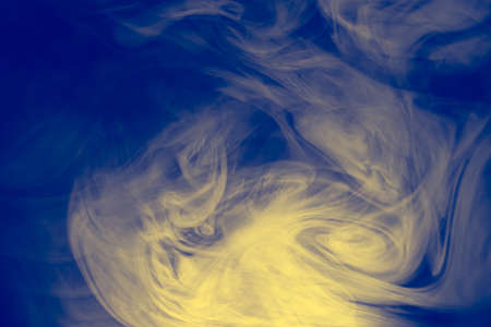 Clouds of colored flowing smoke on a dark background. Smoky extravaganza. Flying smoky vague fantasies. Фото со стока