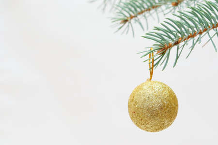 Merry christmas and a happy new year! The atmosphere of the winter holidays. Green spruce branch with decorations on a light background and free space for an inscription.