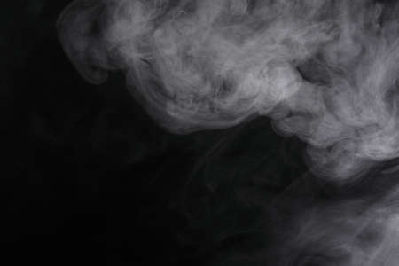 Puffs of white, gray smoke spread on a black background, curling in a fancy dance. Stockfoto