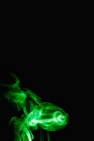 Whimsical curls and shapes of green smoke on a dark background. Streaming smoke from a burning incense stick. 스톡 콘텐츠