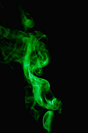 Whimsical curls and shapes of green smoke on a dark background. Streaming smoke from a burning incense stick.
