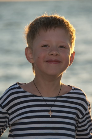 striped vest: boy in a striped vest stands on the background of the sea