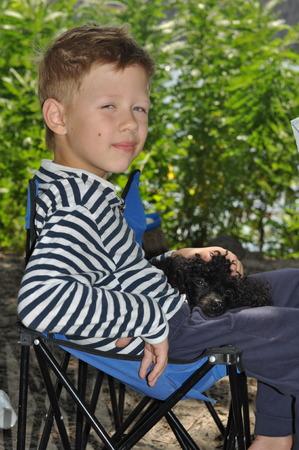 puta: ni�o sentado en una silla azul y en su regazo es un caniche negro Foto de archivo