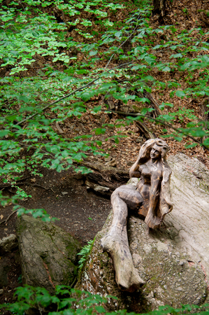 woodland sculpture: Mermaid of wood sitting on a rock in the forest