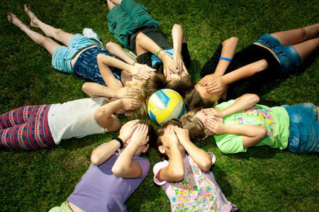 children are around volleyball ball covering her face with palms