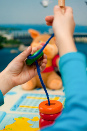 logical: child collects logical toy on a lace