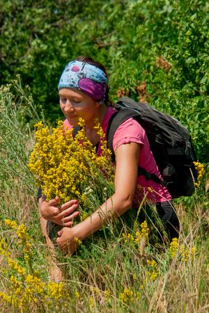 girl hugging shrub with yellow backpack
