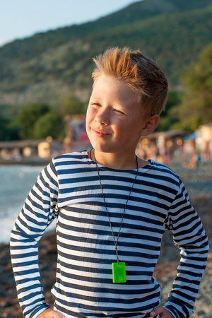 striped vest: boy standing on the beach in summer day striped vest