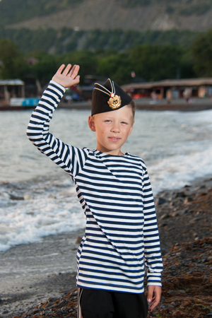 garrison: boy in garrison cap and striped vest standing near the sea on a background of mountains