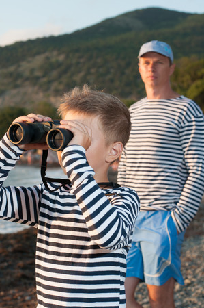striped vest: boy in garrison cap and striped vest standing near the sea with binoculars next to his father in the background of the mountains