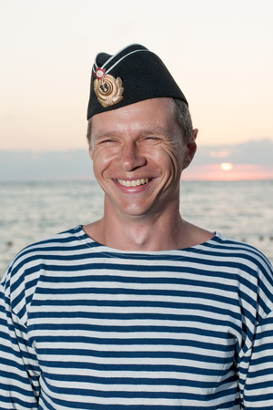 garrison: man standing in garrison cap and striped vest on a background of sea summer day