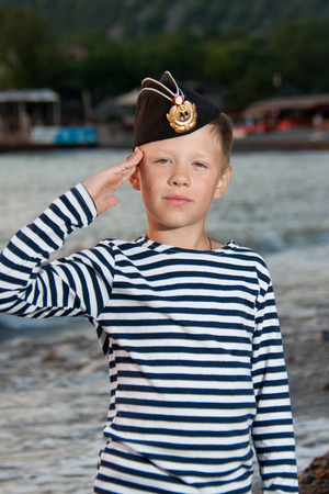 striped vest: boy in garrison cap and striped vest standing near the sea on a background of mountains