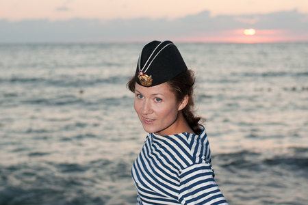 striped vest: beautiful girl in a striped vest and his cap at the sea summer day