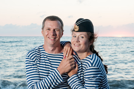 striped vest: man with a woman standing on the background of the sea in his cap and striped vests