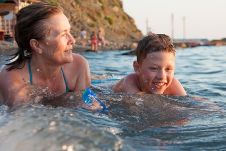 grandmother with her grandson merry and joyful swimming in the sea