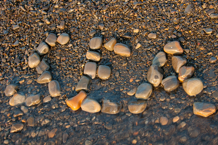 evening out: Sea stones laid out on the beach in the evening sunset